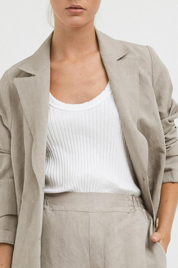 Chaqueta lino color piedra de Mi&Co con solapa larga y bolsillos verticales.