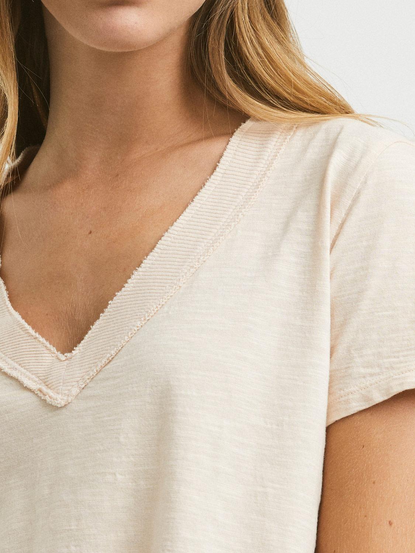 Camiseta peach de algodón 100% de Mi&Co con cuello pico, manga corta con detalles canale