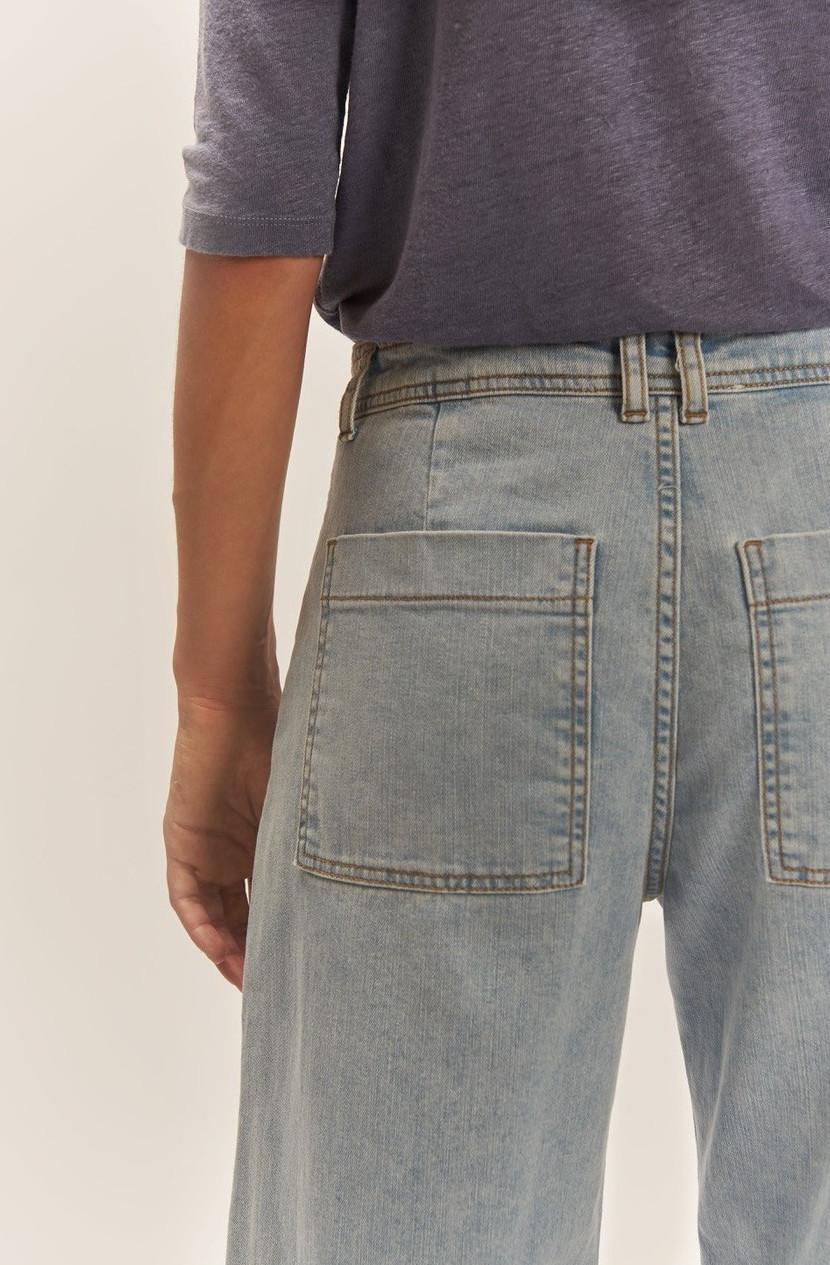Pantalón culotte denim. Efecto palazzo, corte medio alto, cierre con cremallera, botón y cuatro bolsillos.