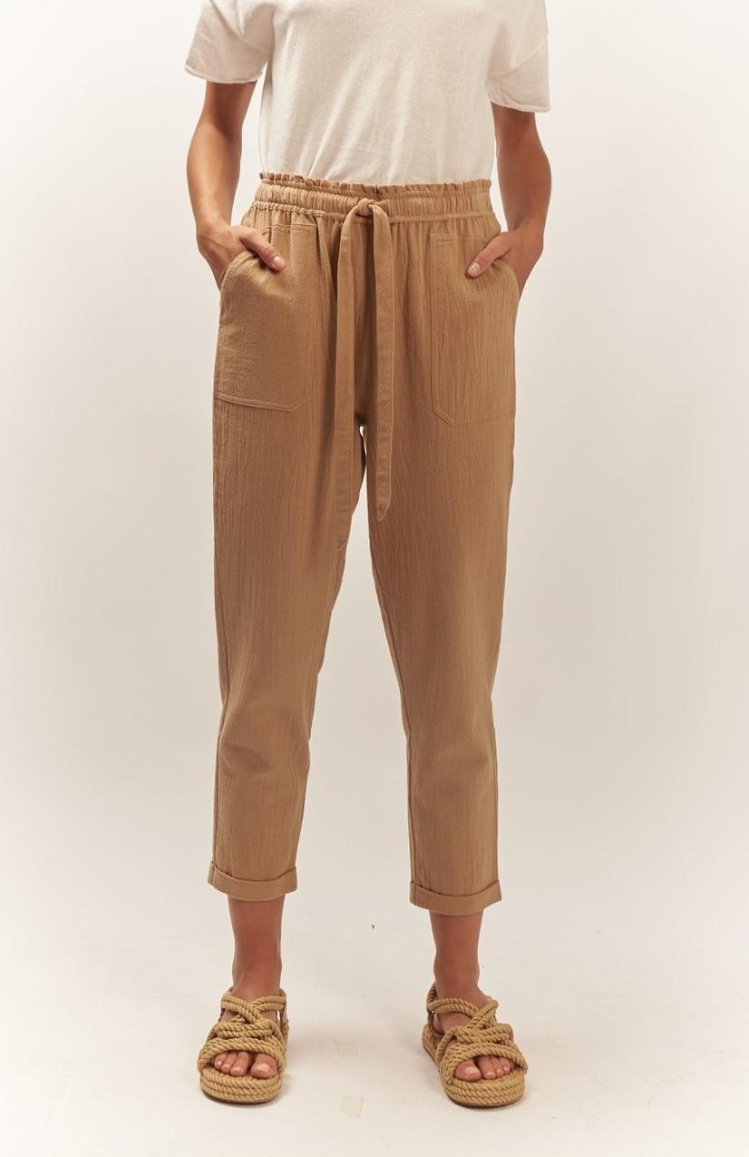 Pantalón beige, con cintura elástica y cinta de ajuste, dos bolsillos y bajo remangado.