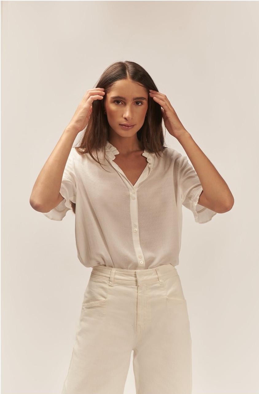 Blusa blanca, cuello con tira y volante, manga amplia con volante, cierre frontal