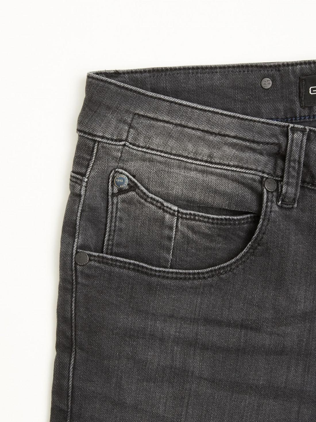 Pantalón gris, efecto lavado, corte recto con cinco bolsillos.