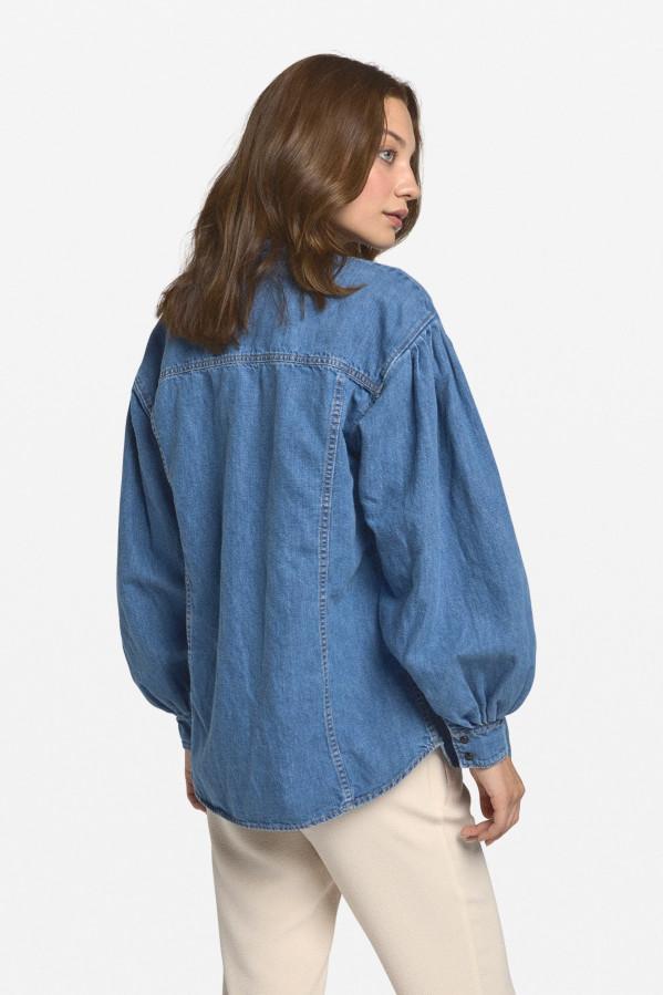 Camisa jeans, estilo holgado con cuello tirilla, cierre delantero y puños con botones automáticos, bolsillos pala, mangas abullonadas. Bajo curvado.